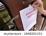 Small photo of Civil servant sticks a notice of eviction of the tenant, close up