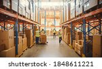 Small photo of Retail Warehouse full of Shelves with Goods in Cardboard Boxes, Workers Scan and Sort Packages, Move Inventory with Pallet Trucks and Forklifts. Product Distribution Delivery Center.