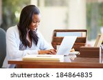 Woman Using Laptop On Desk At...