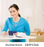 Small photo of Woman writing check from checkbook to pay monthly bills