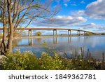 View of lake, trees, grass and bridge on the horizon in a beautiful cloudy day