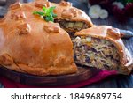 Small photo of Festive Russian pie kurnik with pancakes, chicken and potatoes, cut off piece with layers of filling, horizontal