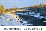 snow covered river flowing under a bridge near Cameron river falls NT