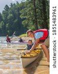 Small photo of Father pushing the kayak into deeper water for canoeing while the son is sitting in it