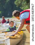 Small photo of Father dragging the kayak in deeper water for canoeing while son is sitting in it and smiling