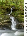 Small photo of Long exposure of a waterfall on the East Lyn river flowing through the woods at Watersmeet in Exmoor National Park