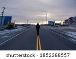 A man walking down the main street of Churchill in northern Manitoba Canada in the start of cold winter.