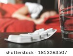 Small photo of Female feeling feeble is laying in her bed - medicines and glass of water on the bedside table - focus on the pills