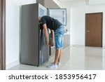 Small photo of On a hot day, the guy cool down with his head in the refrigerator. Broken air conditioner.
