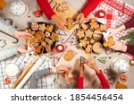 Small photo of Family is decorating a traditional gingerbread. Xmas flat lay. Christmas and New Year holidays mood. Group of people glaze a cookie. Top view of home table
