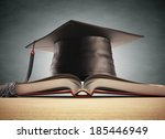 graduation cap over the book... | Shutterstock . vector #185446949