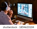 Small photo of Male student wearing headphones taking online course training, watching webinar, remote seminar university class, virtual learning with social distance web teacher, tutor or coach on computer screen.