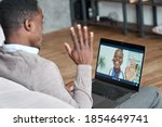 Male black patient talking on conference video call to female african doctor. Virtual therapist consulting young man during online appointment on laptop at home. Telemedicine chat, telehealth meeting - stock photo