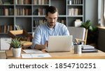 Small photo of Focused business man sit at workplace desk at home office cozy room working on laptop, make analysis sales stats results, learn graphs and making financial forecasts. Busy workday, modern tech concept