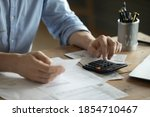 Small photo of Personal finance management, accounting concept. Close up view man sitting at table using calculator performs arithmetic operations calculates costs per month, manage family budget, control expenses
