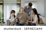 Small photo of Asian elderly senior male grandpa sitting at sofa couch at home living room on quarantine in concept healthcare, chronic health issue or low back pain in retired older people with family.