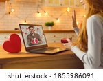 Small photo of Long-distance relationship and virtual date in lockdown. Young couple in love video calling each other during quarantine and showing gifts and presents they prepared for Saint Valentine's Day