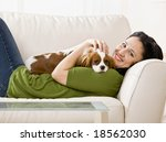 Stock photo relaxed woman laying on sofa holding and petting pet dog 18562030