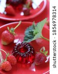 Small photo of Strawberry jelly dessert. Red jelly and strawberries with green leaves in red plates on a bright red background. Berry jelly. Berry diet dessert.