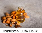 Small photo of Apricot kernel oil in a glass jar closeup on the table and ingredients. Apricot kernel oil and apricot kernels.