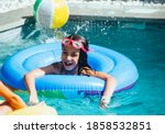 Small photo of Portrait of a little caucasian girl having fun in a pool with a floater