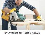 Carpenter working with circular saw - stock photo