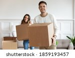 Small photo of Millennial wife and husband holding cardboard boxes standing in cozy living room look at camera relocating to new home. Bank loan and mortgage, tenancy, ownership, parcel delivery services ad concept