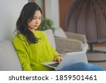 Young Asian Woman Using Laptop...
