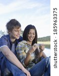 teenage couple using mobile... | Shutterstock . vector #185963375