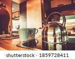 Shiny Metal Water Kettle and Two Cups with Hot Tea Inside RV Camper Van Kitchen Area. Recreational Vehicle Getaway Theme. - stock photo