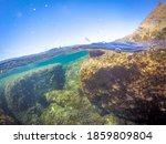 Split underwater view of Alghero rocky shore. Sardinia, Italy - stock photo