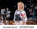 Girl barman creates a cocktail on the alehouse
