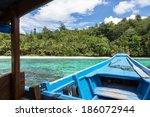 a wooden boat approaches a... | Shutterstock . vector #186072944
