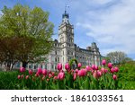 Low angle view of the empire style Parliament Building, home of Quebecs National Assembly in Quebec City with purple tulips in the foreground in the Parliament gardens