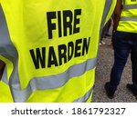 Small photo of Yellow jacket showing fire warden on duty. Safety background.