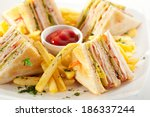 Stock photo club sandwich with cheese pickled cucumber tomato and smoked meat garnished with french fries 186337244