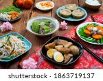 Small photo of Vietnamese table food for Tet, traditional food on lunar new year: pork belly with hard-boiled eggs braised in coconut water, mixed pickles, rice and other Tet foods on background