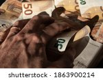 Small photo of A greedy hand grabbing on a bunch of money. Concept for avidity, greed, eagerness and dirty money