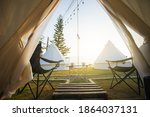 Small photo of The door tent view lookout camping on the mountain in the morning. Glamping camping teepee tent with two empty chairs and table picnic front the door of tent.