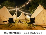Small photo of Group outdoor camping teepee tent and night light with two empty chairs with picnic table and accessories in the forest. Glamping camping tent in the forest under night sky.