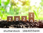 Small photo of Changing year 2020 to 2021 in wooden blocks cubes with growing plant. New year, hope, hello and goodbye concept.