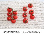 Small photo of The concept of team, cohesion and disunity. Red tomatoes cherry with branches and without branches on white winter background. Selective focus.