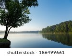 calm lake reflecting trees on a ... | Shutterstock . vector #186499661