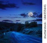 asphalt road going to mountain, passes rural places at night in moon light - stock photo
