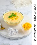 Small photo of A bowl of Mango sago, Hongkong dessert made from mango juice, jelly, sago pearl, evaporated milk and sweetened condensed milk. White background, Selective focus