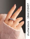 Small photo of Solitaire silver ring on the finger of the lady in a pink sweater. Sterling silver jewelry with nail polish.