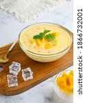 Small photo of A bowl of Mango sago, popular dessert made from mango juice, jelly, sago pearl, evaporated milk and sweetened condensed milk. Served cold, Selective focus