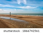 Wooden Beach Pole Reflected In...