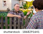 Small photo of neighbors middle aged man and woman chatting near the fence in the village