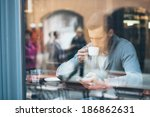 young man drinking coffee in... | Shutterstock . vector #186862631